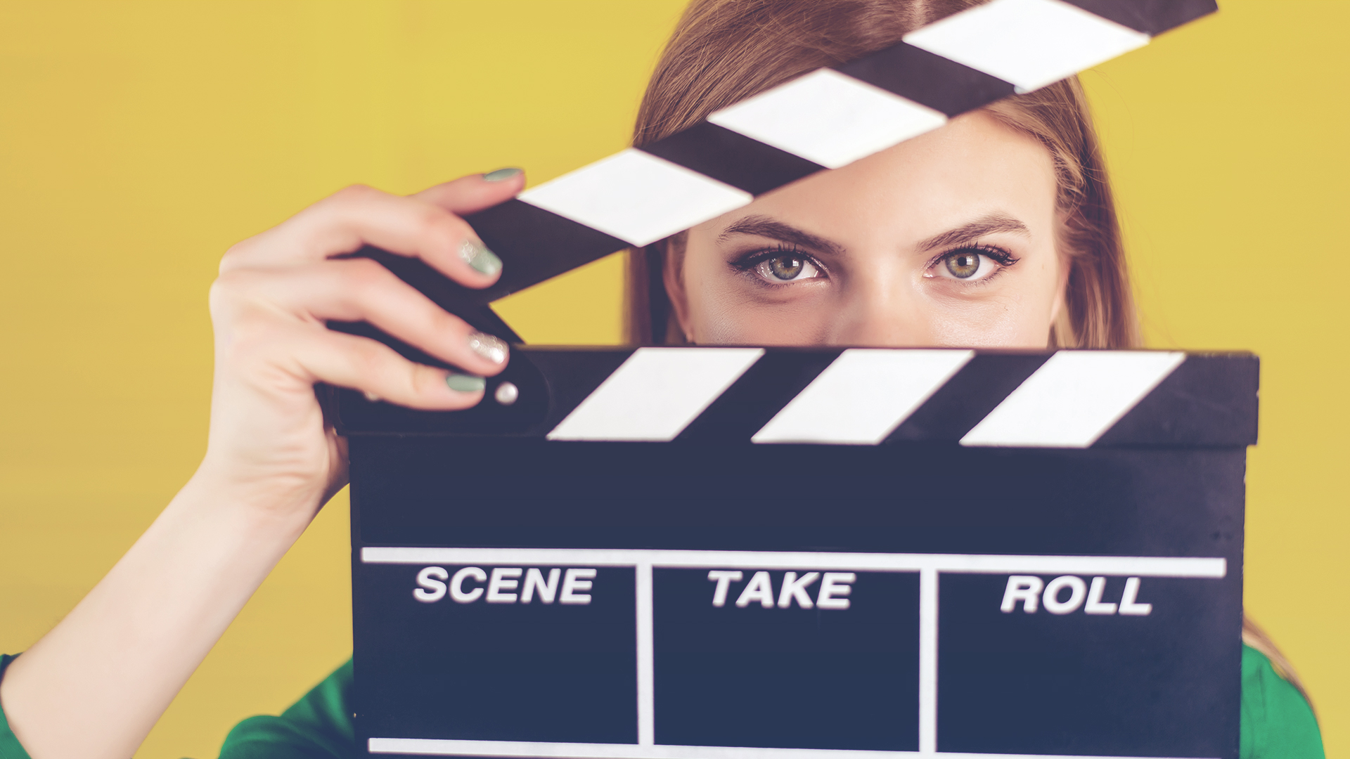 business woman holding clapperboard
